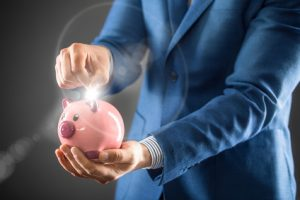 Saving money. Businesman holding pink piggy and putting coin into piggy bank.